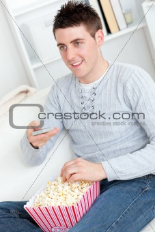 Charming young man eating popcorn watching television in the liv