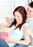 Bright young couple lying on the sofa with popcorn and remote