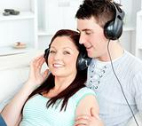 Charming couple listening to music with headphones lying on the