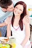 Attentive man kissing his girlfriend during breakfast