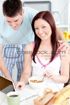 Bright couple using a laptop while breakfast at home in the kitchen