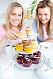 Positive young women eating cakes in the kitchen