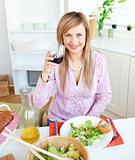 Bright young woman drinking wine and eating a salad in the kitch
