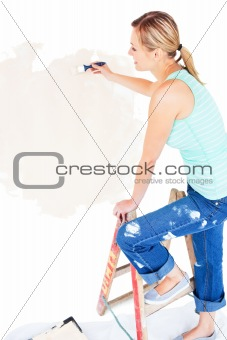 Animated young woman painting a room