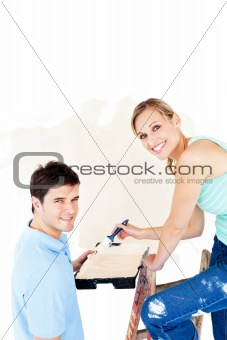 Attractive caucasian couple painting a room