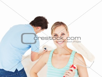 Bright caucasian couple painting a room