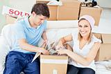 Joyful caucasian couple unpacking boxes with glasses