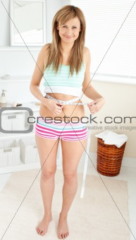Bright caucasian woman measuring her waist with a tape in the ba