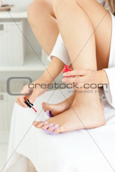 Attractive young woman varnishing her toenails in the bathroom