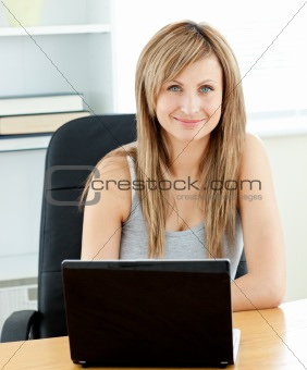 Charismatic young businesswoman using her laptop sitting at her
