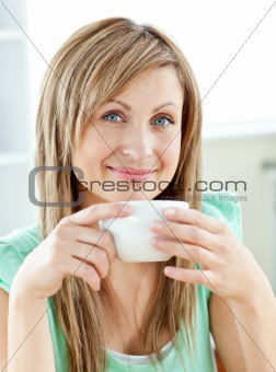 Charming young woman enjoy her coffee sitting in the kitchen