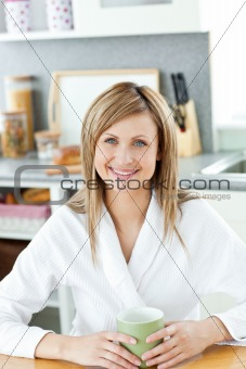Charming woman drinking coffee in the kitchen