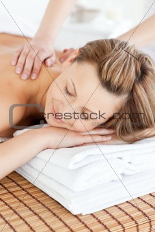 Positive young woman having a back massage