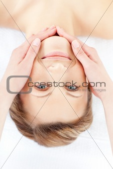 Positive woman receiving a facial massage smiling at the camera