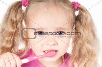 Little cute girl in studio brushing teeth