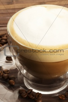 cappuccino in a glass cup on wooden background