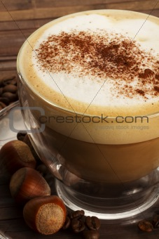 cappuccino with hazelnuts on wooden background
