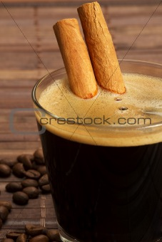 cinnamon sticks inside espresso in a short glass