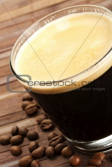 black espresso coffee in a short glass with coffee beans