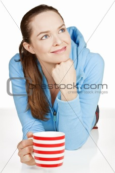 Beautiful healthy woman lying down with cup of tea