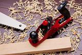 Red plane, wooden brick, handsaw and shavings