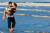 Man Carrying Woman in Romantic Embrace On Beach