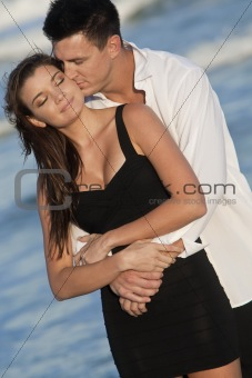 Man and Woman Couple Kissing In Romantic Embrace On Beach