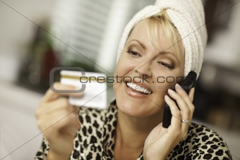 Robed Woman on Cell Phone Looking At Her Credit Card.