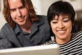 Pretty Smiling Multiethnic Woman and Caucasian Man Using A Laptop Computer Together.