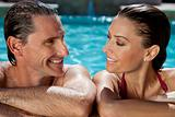 Beautiful Couple Relaxing In Swimming Pool With Perfect Smiles