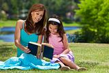 Woman and Girl, Mother and Daughter, Reading a Book Together Out