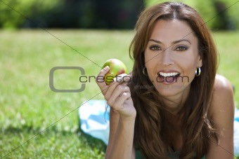 Beautiful Woman Outside Eating An Apple and Smiling