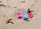 Three beach towels abandoned over sand