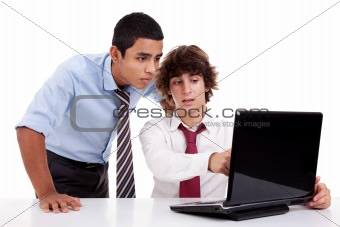 Two young businessmen working together on a laptop, isolated on white, studio shot