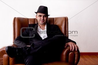 Man with hat seated on a chair