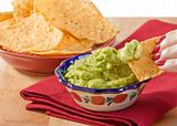 Woman's hand dipping tortilla chip into guacamole