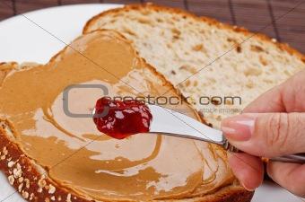 Mom spreading jelly on a peanut butter sandwich
