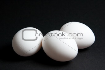 Three white eggs on black background