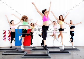group of women doing aerobics on stepper