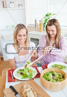 Two merry female friends eating salad in the kitchen