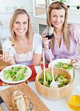 Two positive female friends eating salad in the kitchen