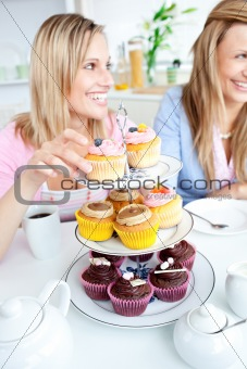 Portrait of two smiling female friends eating pastries