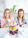Portrait of two female friends eating pastries and drinking coff
