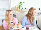 Two laughing female friends eating pastries and drinking coffee