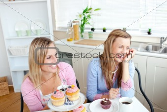 Two cheerful female friends eating pastries and drinking coffee