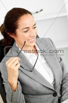Charismatic hispanic businesswoman holding glasses sitting at he