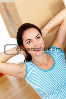 Bright hispanic woman relaxing at the middle of boxes on the flo