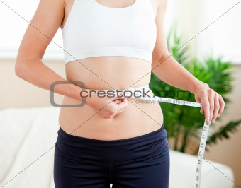 Positive hispanic woman measuring her waist with a tape in the l