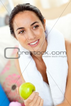 Athletic hispanic woman with a towel holding an apple on the sof