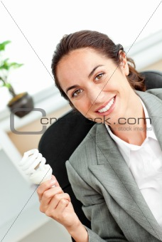 Bright hispanic businesswoman holding a light bulb sitting at he